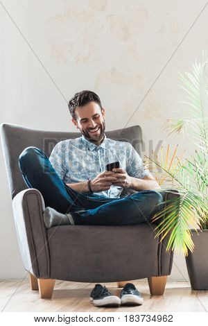 Young man using a smartphone sitting on the armchair