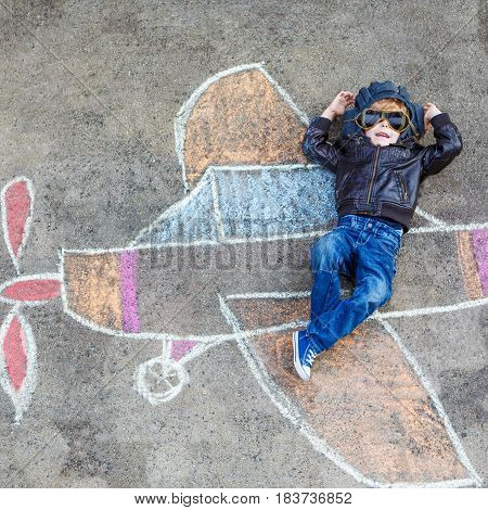 Creative leisure for children: Funny little child of four years having fun with airplane picture drawing with chalk.