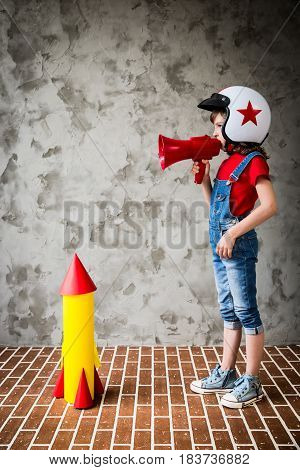 Child Playing With Cardboard Rocket