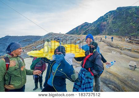 KAWEH IJEN, INDONESIA - 3 MARCH, 2017: Local miner carrying heavy load of yellow sulfur rocks up mountain side, tourist hiking attraction located inside volcanic crater, spectacular nature.