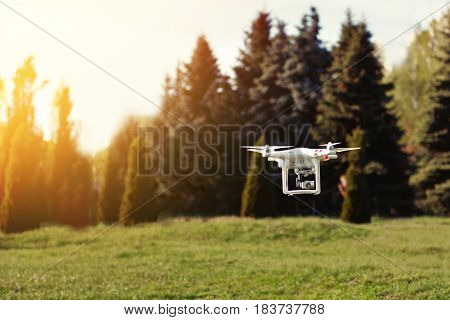 Ukraine Poltavskaya region Kremenchuk - April 26 2017. Quadrocopter flies in the air at sunset. Launching a quadrocopter in the park
