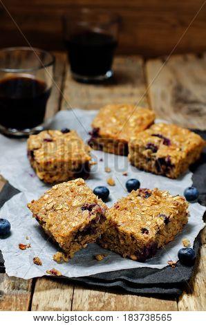 Blueberry Quinoa Oats Breakfast Bars on wood background
