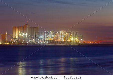 View of the dry cargo ship at the pier in the seaport of Lisbon at night. Portugal.