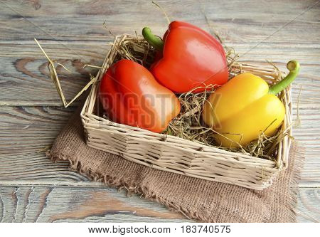 Fresh red and yellow sweet pepper is in a wattled basket.