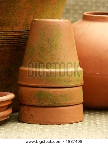 Stack of mossy terra cotta flowerpots among other clay pots poster