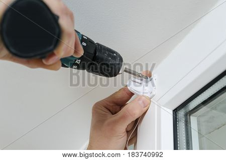 Man's hands attaches a plastic bracket with screwdriver to fix a roller blind on a window.