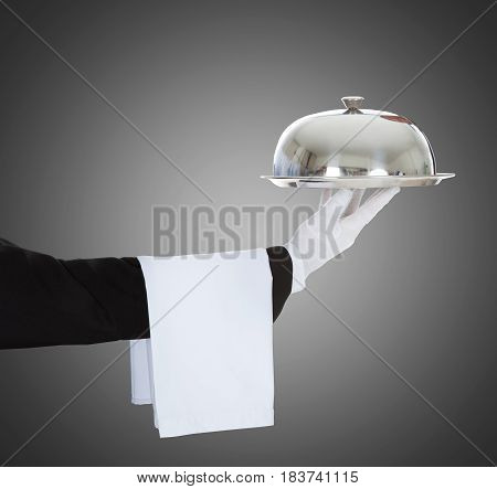 Close-up Of A Waiter's Hand Holding Cloche And Tray On Gray Background
