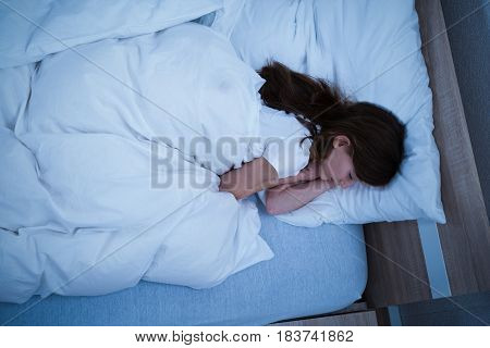 Brunette Girl Sleeping On Cozy Bed With White Blanket