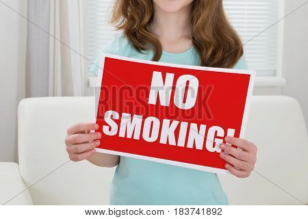 Close-up Of A Girl Holding Banner Showing No Smoking Text