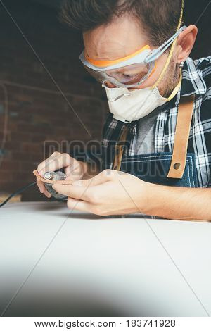 Young worker in protective eyewear and mask polishing rim for glasses.