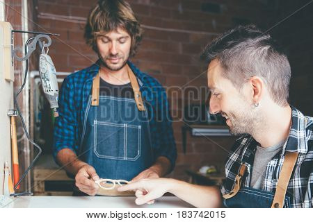 Two young craftsmen in working clothes making rim for glasses.