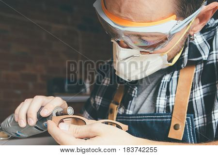 Young artisan in protective eyewear and mask polishing wooden rim for glasses.