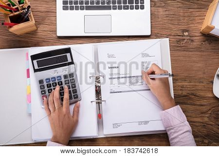 Close-up Of A Businesswoman Calculating Invoice Using Calculator