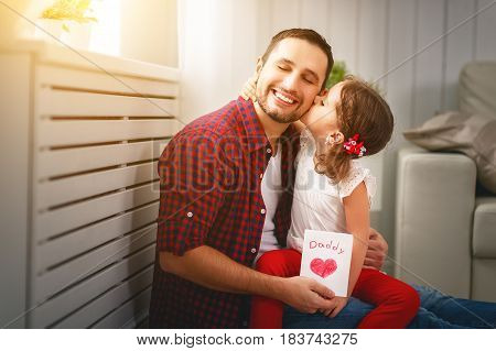 Father's day. Happy family daughter kiss dad and giving greeting card