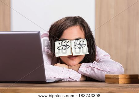 Sleeping Businesswoman Covering His Eyes With The Sticky Notes On Desk At Workplace