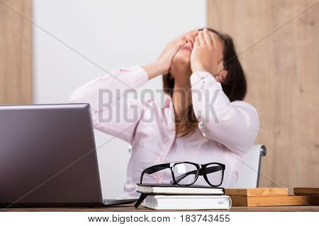 Tired Businesswoman With A Eyeglasses On Diary Over Wooden Desk In Office