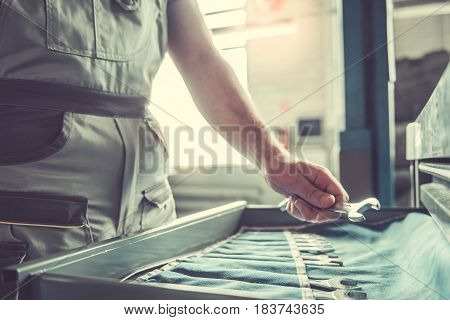 Cropped image of handsome young auto mechanic in uniform choosing tools for repairing car in auto service