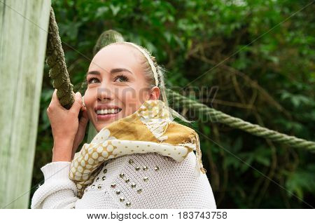 Close up shot if young smiling blond girl sitting in a walking wooden bridge looking peaceful