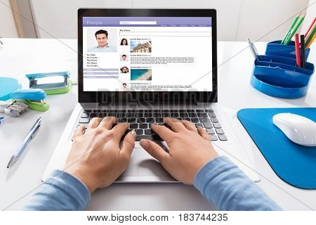 Close-up Of A Businesswoman Chatting On Social Website On Laptop At Workplace
