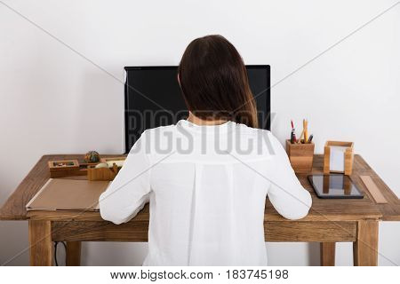 Rear View Of A Woman Using Computer At Home