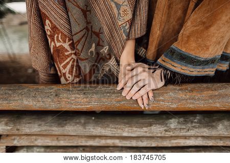 The hands of men and women. A man in a poncho.