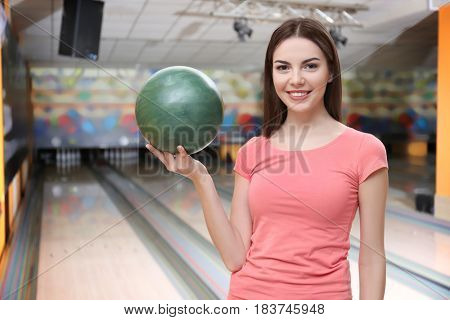 Young woman with ball in bowling club