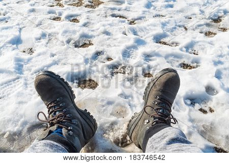 Somebody legs with warm winter shoes on snow. Footwear for cold days