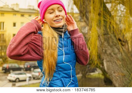 Sports and activities in cold time. Slim fit fitness woman outdoor. Athlete teen girl wearing warm sporty clothes outside listening to music city in the background