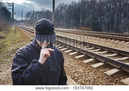 the man in the blank black baseball cap and jacket against the background of railroad