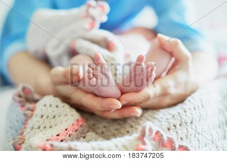 Mother Holding Newborn Baby's Feet In Her Hands