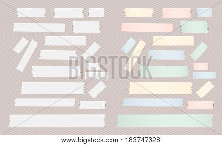 Set of different size colorful and white adhesive, sticky tape paper pieces on squared background.