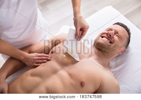 Close-up Of A Person Waxing Man's Chest With Wax Strip