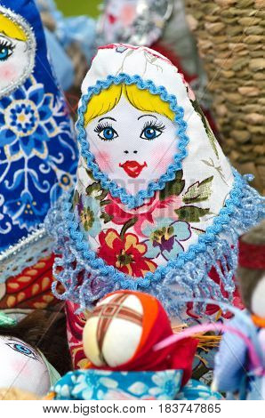 Trade in the market, a colourful traditional doll amulet. Selective focus.