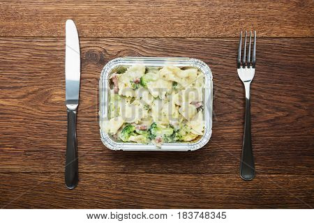 Elevated View Of A Pasta Meal In Foil Container With Fork And Knife
