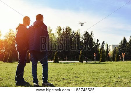 Man controls a quadrocopter. Selective focus on drone men is blurred. Launching a quadrocopter in the park