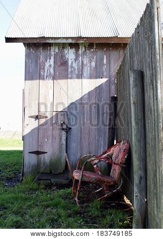Side of faded red barn with vintage orange metal lawn chairs with multi coats of multi colored paint in country farm setting