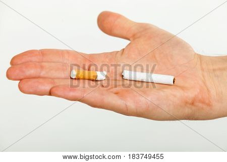 Closeup of broken cigarette on male hand. Winning with addicted nicotine problems stop smoking. Quitting from addiction concept.