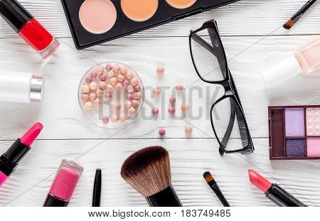 glasses and decorative cosmetics set on white woman table background top view