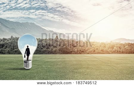 Young businesswoman trapped inside of light bulb on green field