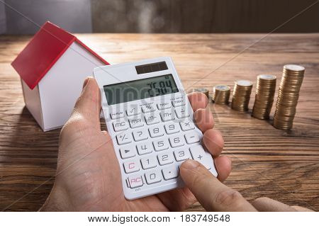 Close-up Of A Person Calculating On Calculator With House Model And Coin Stacked