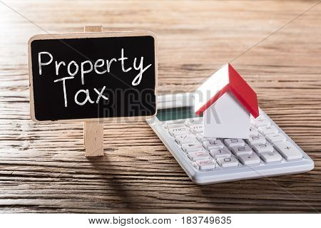Property Tax Written On Blackboard With House Model On Calculator