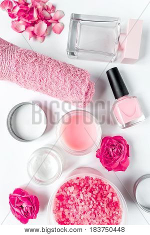 organic cosmetic with rose cream and petals on white background top view