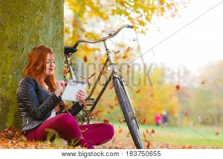 Nature outdoor concept. Smiled girl under the tree. Sitting and enjoying autumnal weather.