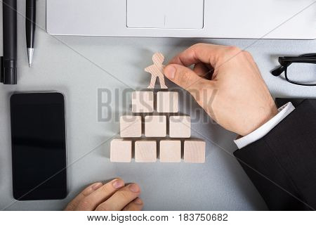 Close-up Of A Businessperson Arranging Human Figure Cut Out On Top Of The Wooden Blocks