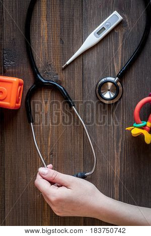 children's doctor work with stethoscope and toys on wooden desk background top view