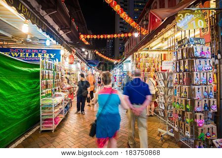 SINGAPORE - MARCH 5: Shoppers walk through a Chinatown market at night on March 5 2015 in Singapore. The city state's ethnic Chinese began settling in Chinatown circa 1820s.