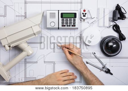 Close-up Of A Male Engineer Working On Blueprint With Security Equipments