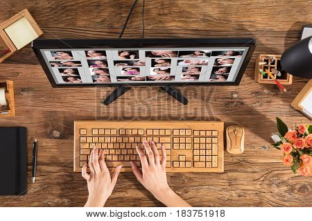 Female Designer Using Wooden Keyboard With Set Of Women's Picture On Computer Screen