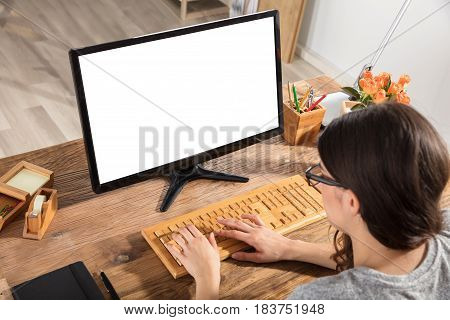 Close-up Of A Businesswoman Using Wooden Keyboard With Blank Screen On Computer At Workplace