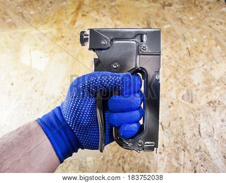 Worker hand in blue dotted gloves holding steel industrial stapler and nailing memo paper on a wooden surface board.